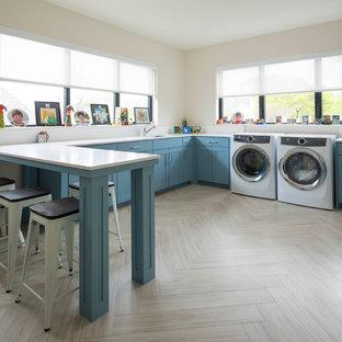 Inredning av ett klassiskt vit u-format vitt grovkök, med en undermonterad diskho, skåp i shakerstil, blå skåp, vita väggar, bambugolv, en tvättmaskin och torktumlare bredvid varandra och brunt golv