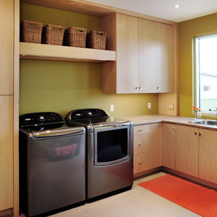 Inspiration for a mid-sized contemporary l-shaped utility room in Toronto with a drop-in sink, flat-panel cabinets, light wood cabinets, green walls and a side-by-side washer and dryer.