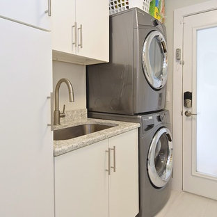 Inspiration for a small traditional single-wall dedicated laundry room in Tampa with an undermount sink, flat-panel cabinets, white cabinets, white walls, laminate floors, a stacked washer and dryer and white floor.