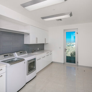 Design ideas for a large modern single-wall utility room in Phoenix with a submerged sink, flat-panel cabinets, white cabinets, quartz worktops, white walls, marble flooring, a side by side washer and dryer and grey floors.