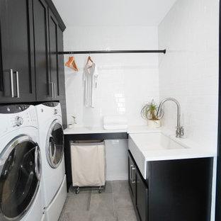 Immagine di una grande lavanderia minimal con ante lisce, ante nere, pareti grigie, pavimento in gres porcellanato e pavimento grigio