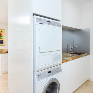 Design ideas for a contemporary laundry room in Brisbane with onyx benchtops, a stacked washer and dryer, beige floor and multi-coloured benchtop.
