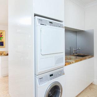 Inredning av en modern flerfärgade flerfärgat tvättstuga, med bänkskiva i onyx, en tvättpelare och beiget golv