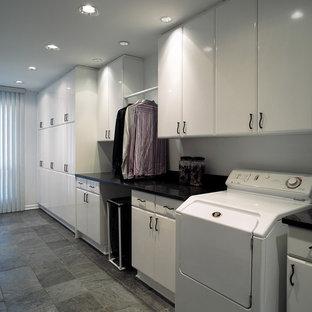 Inspiration för ett mellanstort funkis svart linjärt svart grovkök, med släta luckor, vita skåp, granitbänkskiva, vita väggar, skiffergolv och en tvättmaskin och torktumlare bredvid varandra