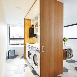 Idéer för små funkis linjära små tvättstugor, med släta luckor, vita väggar, en tvättmaskin och torktumlare bredvid varandra och skåp i mellenmörkt trä