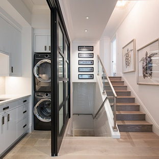 Inspiration for a contemporary l-shaped medium tone wood floor and brown floor dedicated laundry room remodel in Tampa with an undermount sink, flat-panel cabinets, white cabinets, white walls, a stacked washer/dryer and white countertops
