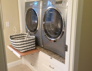 Contemporary Laundry room with raised washer dryer, white cabinets, drawer slide
