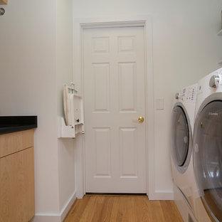Idee per una piccola sala lavanderia contemporanea con lavello sottopiano, ante lisce, ante in legno chiaro, top in saponaria, pareti bianche, pavimento in legno massello medio, lavatrice e asciugatrice affiancate, pavimento arancione e top nero