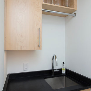 Inspiration for a small contemporary galley separated utility room in Raleigh with a submerged sink, flat-panel cabinets, light wood cabinets, soapstone worktops, white walls, medium hardwood flooring, a side by side washer and dryer, orange floors and black worktops.
