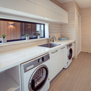 Photo of a large scandi galley utility room in Christchurch with a built-in sink, white cabinets, laminate countertops, white walls, ceramic flooring, a side by side washer and dryer, grey floors and flat-panel cabinets.