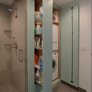 Idéer för en modern tvättstuga, med släta luckor, klinkergolv i porslin, en tvättpelare och blå skåp