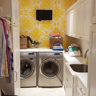 Idee per una piccola lavanderia multiuso bohémian con lavello sottopiano, ante con bugna sagomata, ante bianche, pareti gialle, pavimento con piastrelle in ceramica e lavatrice e asciugatrice affiancate