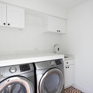 Esempio di una sala lavanderia chic con lavello sottopiano, ante con riquadro incassato, ante bianche, top in quarzite, pareti bianche, pavimento con piastrelle in ceramica, lavatrice e asciugatrice affiancate, pavimento arancione e top bianco