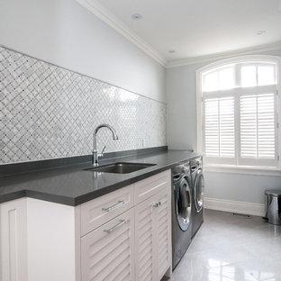Immagine di una grande sala lavanderia design con lavello sottopiano, ante a persiana, ante bianche, top in granito, pareti grigie, pavimento in marmo e lavatrice e asciugatrice affiancate