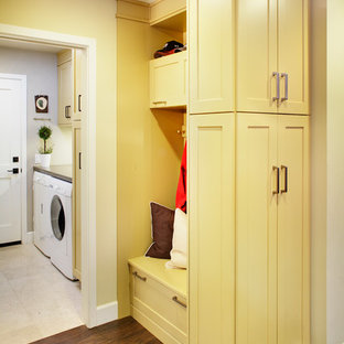 Example of a mid-sized classic single-wall dark wood floor dedicated laundry room design in Sacramento with shaker cabinets, yellow cabinets, quartz countertops, a side-by-side washer/dryer and beige walls