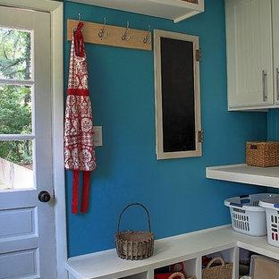 Idee per una grande lavanderia multiuso classica con ante in stile shaker, ante bianche, top in legno, pareti blu, pavimento con piastrelle in ceramica, lavatrice e asciugatrice a colonna, pavimento beige e top bianco
