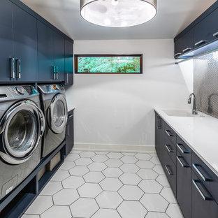 Modern inredning av en vita parallell vitt tvättstuga, med en undermonterad diskho, släta luckor, blå skåp, vita väggar och vitt golv