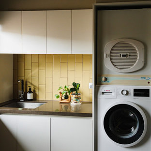 Design ideas for a mid-sized contemporary galley dedicated laundry room in Melbourne with flat-panel cabinets, ceramic splashback, quartz benchtops, an undermount sink, white cabinets, yellow splashback, slate floors, a stacked washer and dryer, multi-coloured floor and brown benchtop.