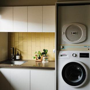 Foto på en mellanstor funkis bruna parallell tvättstuga enbart för tvätt, med släta luckor, stänkskydd i keramik, bänkskiva i kvarts, en undermonterad diskho, vita skåp, gult stänkskydd, skiffergolv, en tvättpelare och flerfärgat golv