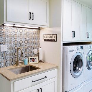 Esempio di una sala lavanderia classica con lavello sottopiano, ante in stile shaker, ante bianche, lavatrice e asciugatrice affiancate, pavimento bianco e top beige