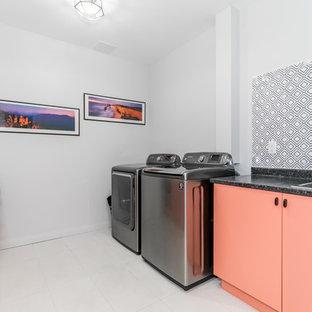 Cette photo montre une buanderie linéaire moderne dédiée et de taille moyenne avec un évier posé, un placard à porte shaker, des portes de placard oranges, un mur blanc, des machines côte à côte, un sol blanc et un plan de travail noir.
