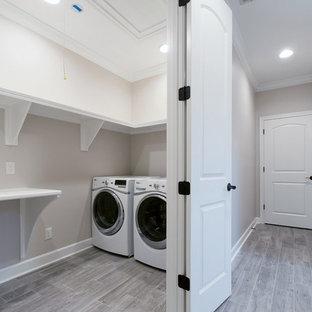 Inredning av en klassisk mellanstor turkosa turkost liten tvättstuga, med grå väggar, klinkergolv i keramik, en tvättmaskin och torktumlare bredvid varandra och flerfärgat golv