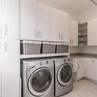 Exempel på en mellanstor modern l-formad tvättstuga enbart för tvätt, med en undermonterad diskho, släta luckor, ljust trägolv och en tvättmaskin och torktumlare bredvid varandra