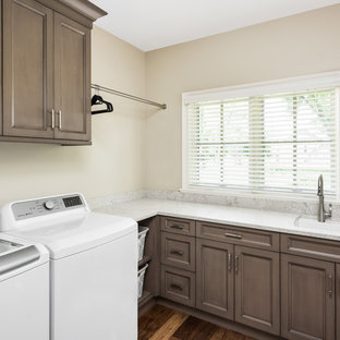 Dedicated laundry room - mid-sized traditional l-shaped dark wood floor and brown floor dedicated laundry room idea in Chicago with an undermount sink, recessed-panel cabinets, brown cabinets, quartz countertops, beige walls, a side-by-side washer/dryer and white countertops