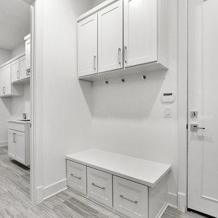 Inredning av en klassisk vita vitt tvättstuga, med en undermonterad diskho, skåp i shakerstil, vita skåp, bänkskiva i onyx, vita väggar, klinkergolv i porslin, en tvättmaskin och torktumlare bredvid varandra och grått golv
