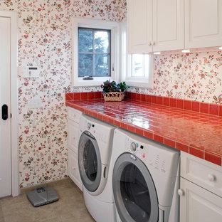Aménagement d'une buanderie linéaire classique dédiée avec un placard avec porte à panneau surélevé, des portes de placard blanches, un plan de travail en carrelage, un mur multicolore, des machines côte à côte, un sol gris et un plan de travail rouge.