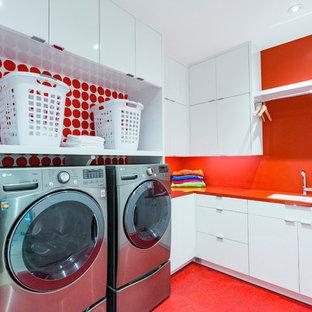 Modern inredning av en röda l-formad rött tvättstuga enbart för tvätt, med en undermonterad diskho, släta luckor, vita skåp, bänkskiva i koppar, röda väggar, linoleumgolv, en tvättmaskin och torktumlare bredvid varandra och rött golv