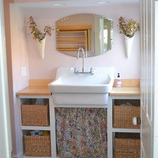 Idée de décoration pour une buanderie champêtre multi-usage et de taille moyenne avec un évier de ferme, un placard sans porte, des portes de placard blanches, un plan de travail en bois, un mur rose, un sol en vinyl, des machines superposées et un sol marron.