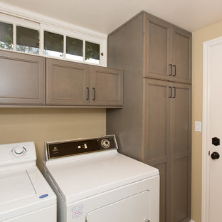 Example of a small transitional single-wall porcelain tile dedicated laundry room design in Orange County with recessed-panel cabinets, beige walls, a side-by-side washer/dryer and brown cabinets