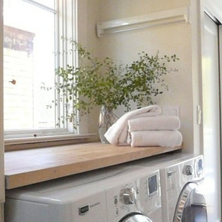 Small transitional galley dark wood floor utility room photo in San Francisco with wood countertops, white walls and a side-by-side washer/dryer