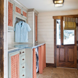 Photo of a mid-sized country single-wall utility room in Denver with a drop-in sink, stainless steel benchtops, travertine floors and a side-by-side washer and dryer.