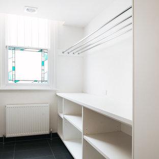 Modelo de lavadero multiusos, ecléctico, grande, con armarios con paneles lisos, puertas de armario blancas, encimera de cuarzo compacto, paredes beige, suelo de baldosas de cerámica y lavadora y secadora juntas
