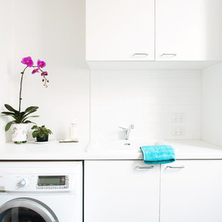 Inspiration for a large contemporary single-wall ceramic floor utility room remodel in Melbourne with a single-bowl sink, flat-panel cabinets, white cabinets, quartz countertops, white walls, a side-by-side washer/dryer and white countertops