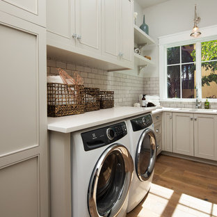 Coastal l-shaped light wood floor dedicated laundry room photo in Miami with an undermount sink, recessed-panel cabinets, beige cabinets, gray walls and white countertops