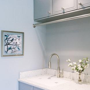 Foto på en vintage tvättstuga, med bänkskiva i återvunnet glas, klinkergolv i porslin, en undermonterad diskho, blå väggar, en tvättmaskin och torktumlare bredvid varandra och grå skåp
