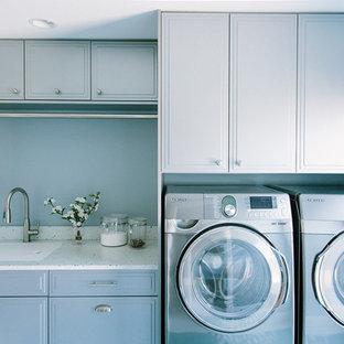 Inredning av en klassisk tvättstuga, med bänkskiva i återvunnet glas, klinkergolv i porslin och grå skåp