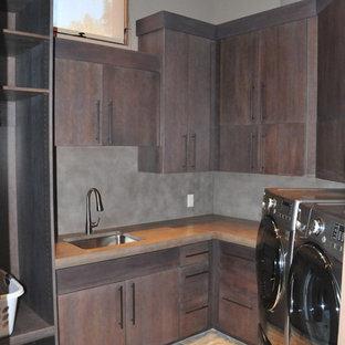 Ispirazione per una sala lavanderia chic di medie dimensioni con top in cemento, lavello sottopiano, ante lisce, ante in legno bruno, pareti grigie, pavimento in ardesia, lavatrice e asciugatrice affiancate, pavimento multicolore e top grigio