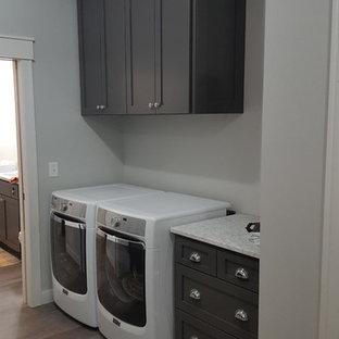 Idee per una sala lavanderia shabby-chic style di medie dimensioni con lavello stile country, ante lisce, ante grigie, top in granito, pareti grigie, pavimento in vinile, lavatrice e asciugatrice affiancate, pavimento grigio e top bianco