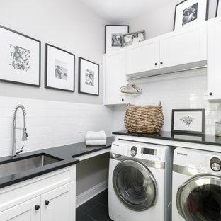Inspiration för en lantlig svarta l-formad svart tvättstuga, med en undermonterad diskho, skåp i shakerstil, vita skåp, vitt stänkskydd, stänkskydd i tunnelbanekakel, grå väggar, en tvättmaskin och torktumlare bredvid varandra och svart golv