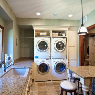 Ispirazione per una lavanderia stile rurale con lavello stile country, top in superficie solida e lavatrice e asciugatrice a colonna