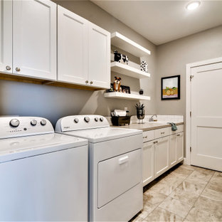 Photo of a mid-sized country single-wall utility room in Denver with a drop-in sink, shaker cabinets, white cabinets, quartzite benchtops, white splashback, subway tile splashback, grey walls, porcelain floors, a side-by-side washer and dryer, grey floor, grey benchtop and planked wall panelling.