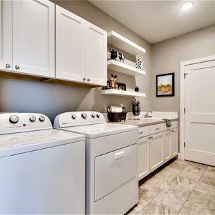 Lantlig inredning av ett mellanstort grå linjärt grått grovkök, med en nedsänkt diskho, skåp i shakerstil, vita skåp, bänkskiva i kvartsit, vitt stänkskydd, stänkskydd i tunnelbanekakel, grå väggar, klinkergolv i porslin, en tvättmaskin och torktumlare bredvid varandra och grått golv
