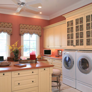 This is an example of a traditional laundry room in Miami with pink walls and white cabinets.