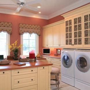 Cette photo montre une buanderie chic avec un mur rose et des portes de placard blanches.