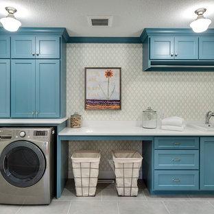 Cette photo montre une très grand buanderie linéaire tendance dédiée avec des portes de placard bleues, des machines côte à côte, un évier posé, un placard à porte shaker, un plan de travail en marbre, un mur gris et un sol en ardoise.