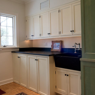 This is an example of a medium sized classic single-wall utility room in Philadelphia with a belfast sink, beaded cabinets, white cabinets, soapstone worktops, white walls, light hardwood flooring, a concealed washer and dryer, brown floors and black worktops.